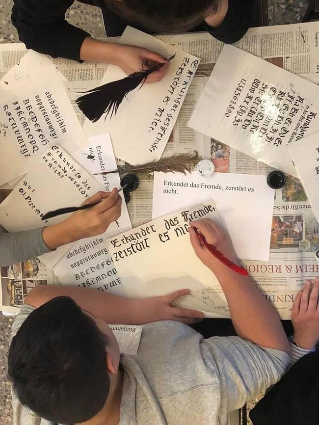 Schüler*innen schreiben mit Federn